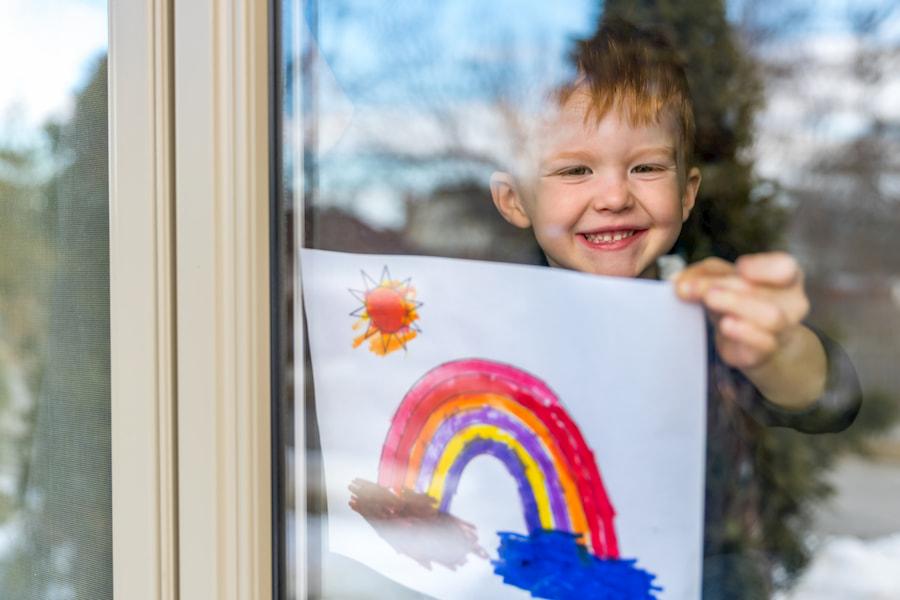 Junge hängt Bild an Fenster auf