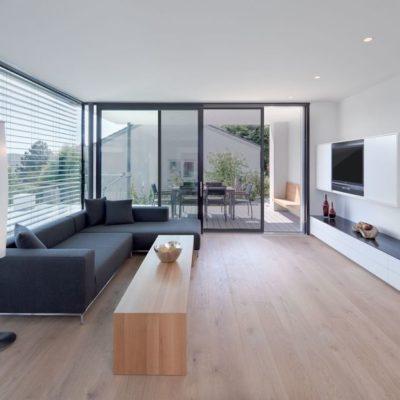 Einblick-in-ein-Wohnzimmer-mit-dunkelgrauer-Couch-und-Terassentuer-mit-Schieberahmen-Insektenschutz